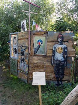 """Das Kürzel L.E.T. wird als """"Les Enfants Terribles"""" aufgeschlüsselt und lässt auf die französischen Wurzeln des Künstlers schließen. L.E.T. gehört zu den ersten deutschen Street Artists: bis heute ist er auf der Straße aktiv und prägt das Bild seiner Heimatstadt Düsseldorf. Seine Motive sprüht er auf Papier und plakatiert sie dann als Cutout in der Stadt. L.E.T. lässt sich von bekannten Werken inspirieren, wobei er oftmals die charmante, provokante und witzige englische Street-Art zitiert. In seinen Neuinterpretationen verfolgt er einen sozialkritischen Ansatz, der die Missstände unserer Konsum- und Spaßgesellschaft identifiziert. Cubus Im Rahmen des Werks Cubus werden Stencils auf alten & gefundenen Holzplanken, Türen, Fenster, Leinwände & Altmetall. Diese werden zu einen Cubus zusammengebaut."""